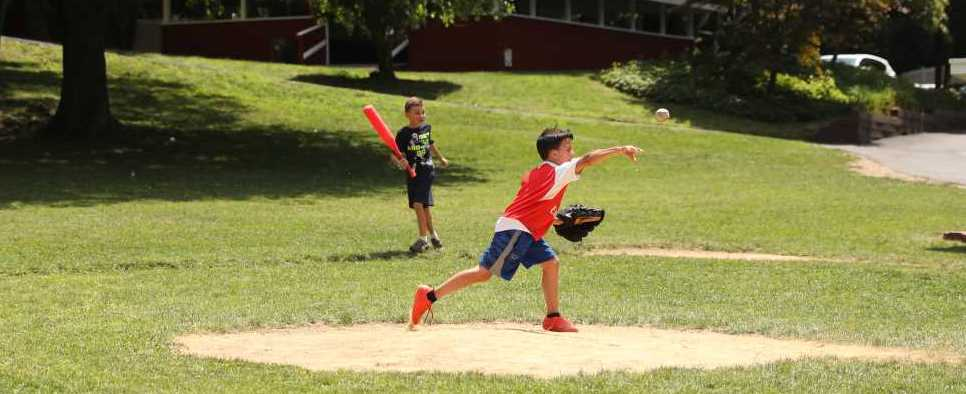 Camper Pitching a Baseball Towards the Batter