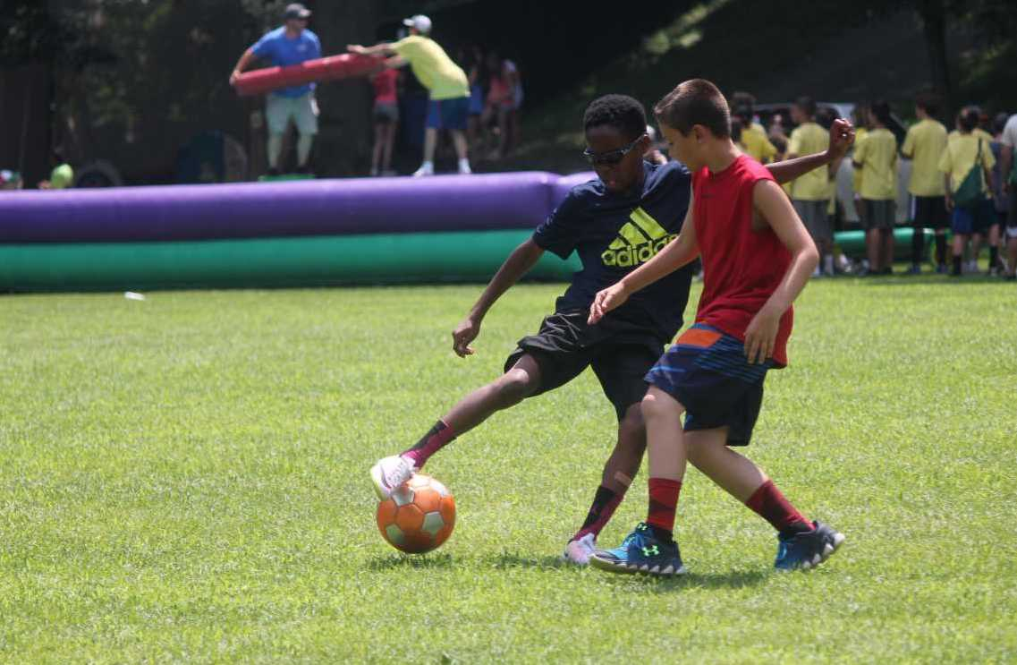 Two Campers Dribbling a Soccer Ball
