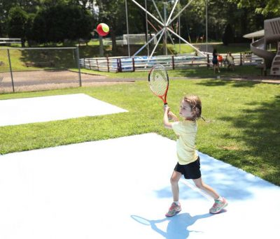 Little Girl Hitting a Tennis Ball