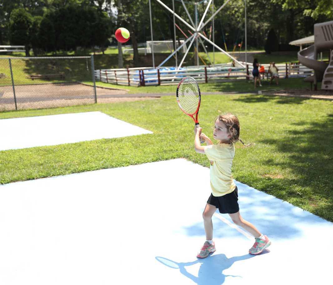 Little Girl Hitting a Tennis Ball