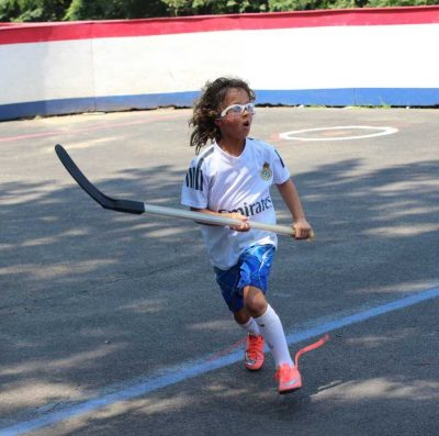Child Holding a Hockey Stick in the Middle of a Hockey Game