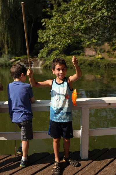Camper holding up a fish he caught at the lake.