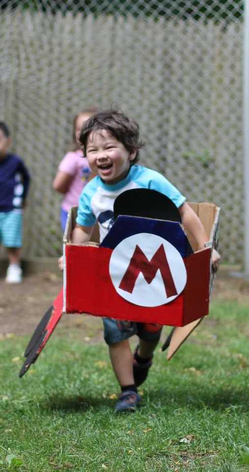 Preschool Camper Laughing and Driving a Cardboard Mario Kart Car
