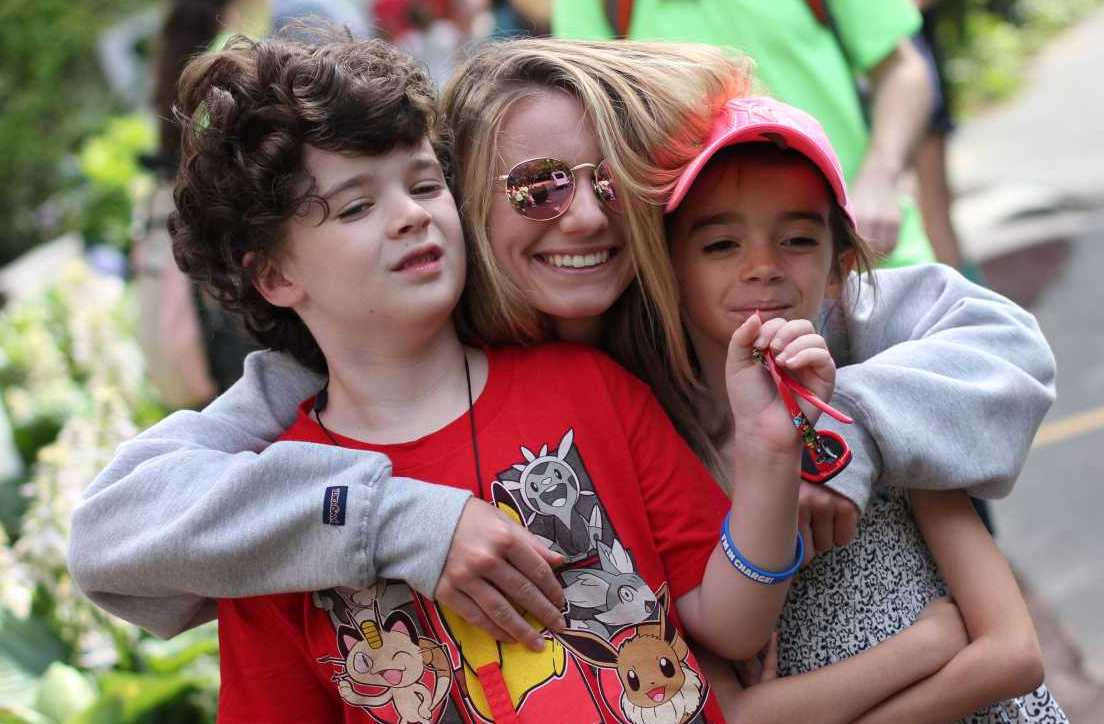 Counselor Hugging Two Young Special Needs Campers