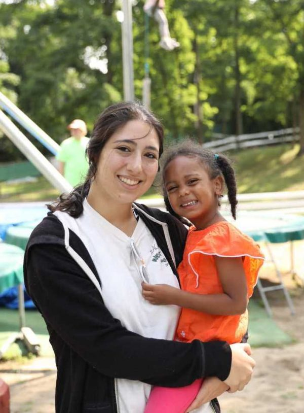 West Hills Day Camp Counselor Holding a Toddler Camper Smiling for A Picture