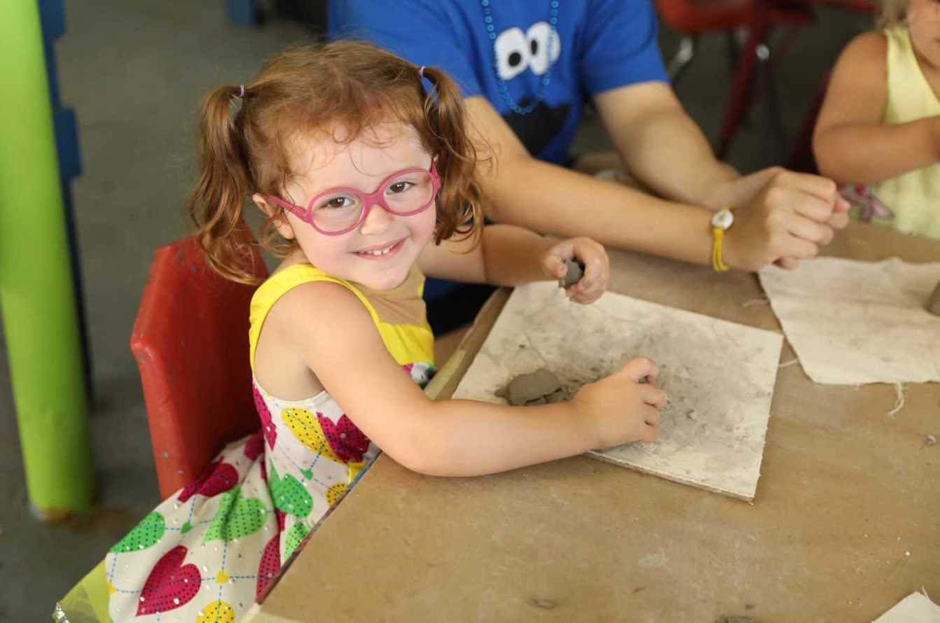 Toddler with Glasses Smiling and Doing Arts and Crafts