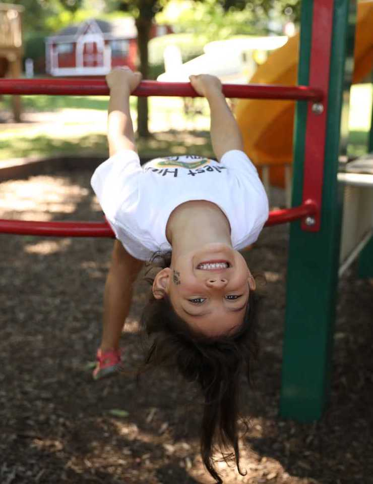 Young Camper hanging from climbing bars on the playground