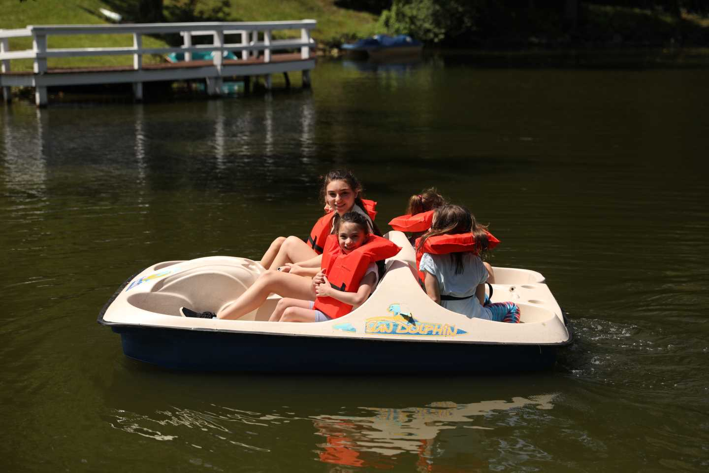 Campers on a paddle boat with life jackets on.
