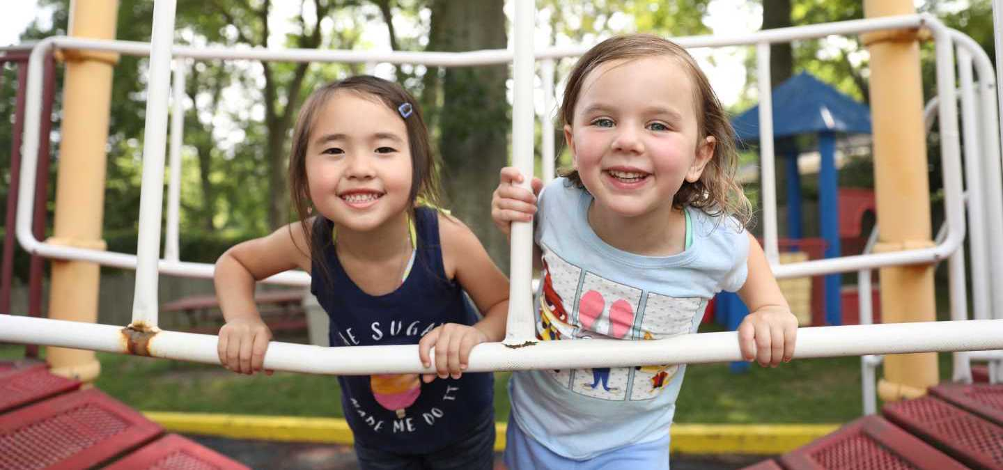 Two preschool age girls smiling on the playground