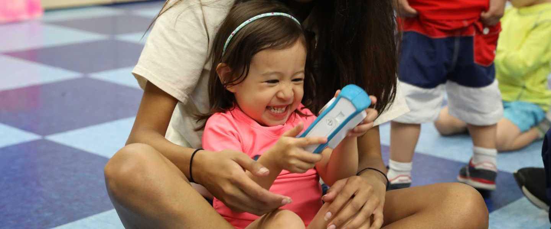 Toddler Camper Laughing and Exploring a Digital Camera