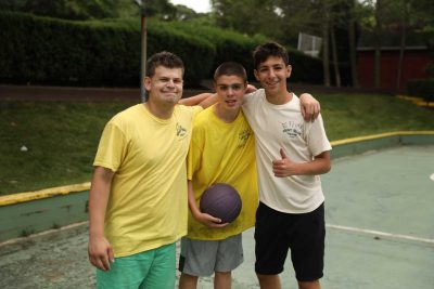 Two Campers on the Autism Spectrum and Their Counselors Posing with a Basketball on the Basketball Court