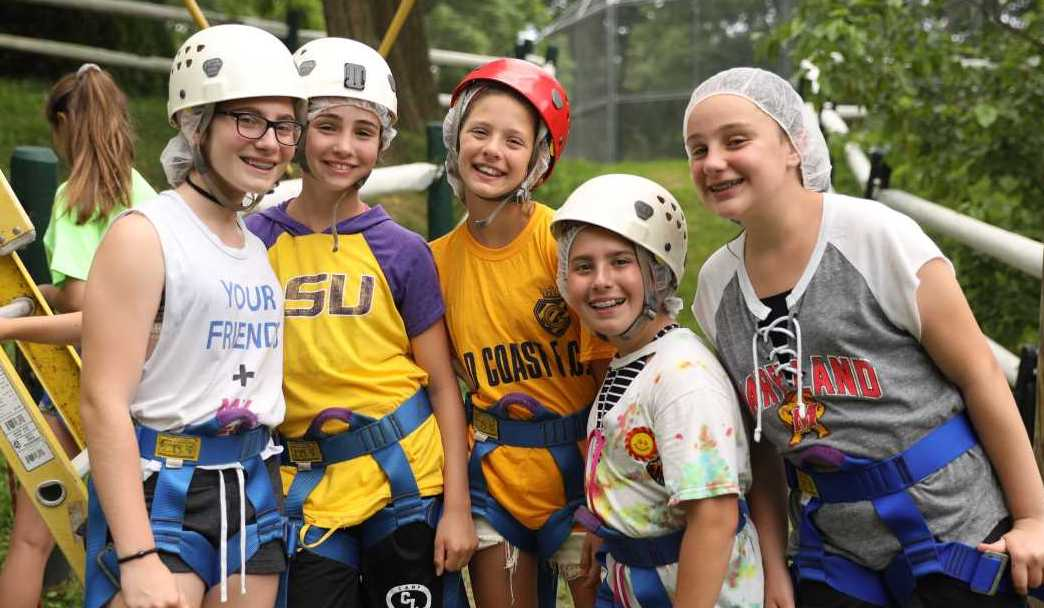 Group of Girls With Helmets and Harnesses on Waiting to Ride the Zip Line