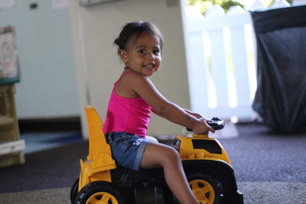 Toddler Camper on a Toy Truck Smiling at the Camera