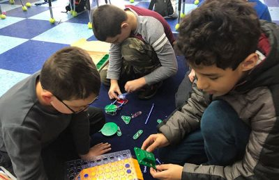 Three Students Working Together On a STEM Building Project