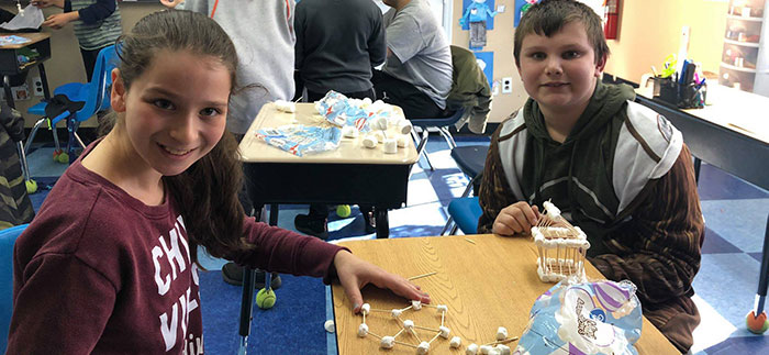 Two Students Working on Marshmallow Building ACtivity on a Desk