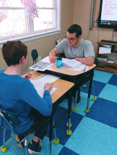 Two Students Sitting in Desks Across From Each Other Working Together