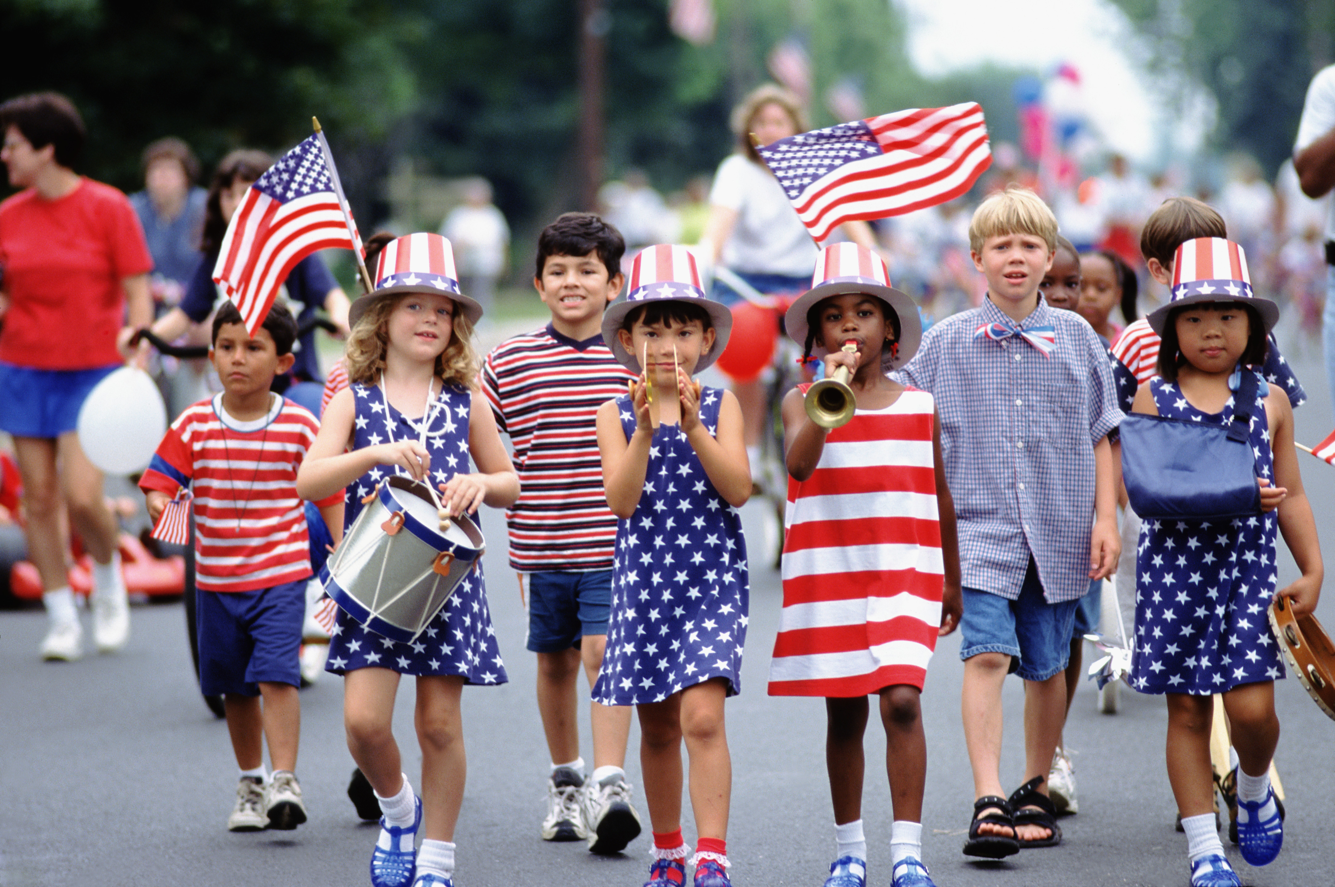 Children dressed in American Flag Clothing Marching in an Independence Day Parade